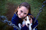 Young girl holding her puppy ( Jack Russell Terrier) intensely looking at camera on swing smiling