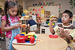 "September 14, 2011. Raleigh, NC. . Ashely Fuentes-Banegas and Jeffrey Hernandez-Valladares play at the ""restaurant"".. Project Enlightenment, a public pre-kindergarten program for at risk children, has been threatened with closure due to state wide budget cuts.."