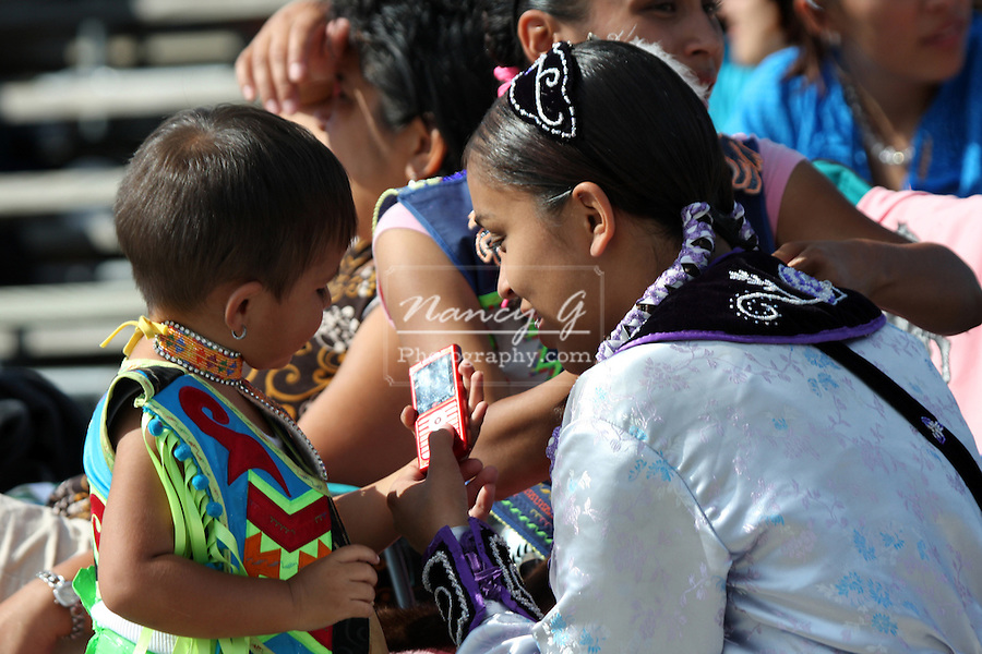 A Native American Indian mom showing a cell phone to her son at a Pow Wow at the Milwaukee Lakefront Indian Summer Festival, Wisconsin