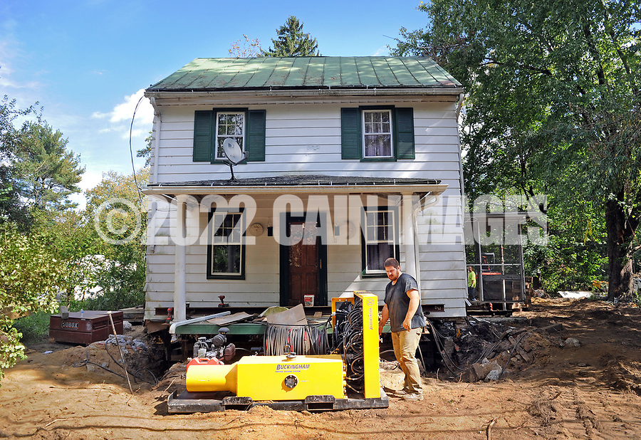 Nate Champ of Bernville, Pennsylvania, with Wolfe House & Building Movers works the controls as they raise a house on Church Street 4 feet off the ground Friday, September 29, 2017 Lumbertown, New Jersey. Many homes along the Rancoacas Creek are being raised as protection from future flooding. The house is raised one foot at a time. (WILLIAM THOMAS CAIN / For The Philadelphia Inquirer)