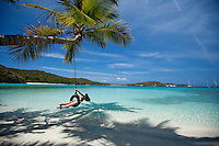 Young woman on a tire swing at  Gibney / Oppenheimer Beach.Virgin Islands National Park.St. John, U.S. Virgin Islands