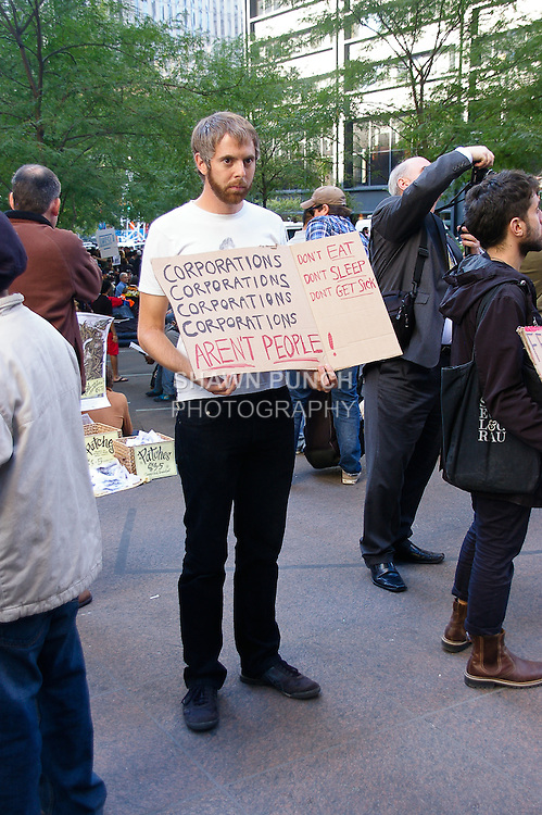 """Protester holds """"Corporations Aren't People sign"""" at the Occupy Wall Street Protest in New York City October 6, 2011."""
