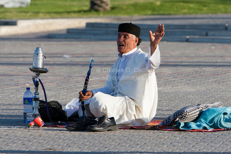 Tripoli, Libya, North Africa - Man with Water Pipe, Sheesha, in Public Park near the Green Square, downtown Tripoli.  He wears a Juba, a light-weight ankle-length garment and a black chechia, a Tunisian-made hat.