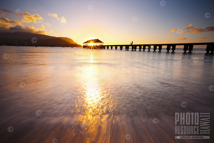 The sun sets through the Hanalei Pier, Kauai
