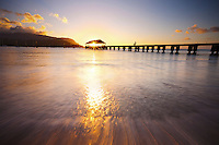 The sun sets through the Hanalei Pier, Kauai