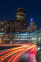 Saint Paul, Minnesota skyline at night with flowing traffic lights on Interstate 94 in the foreground.