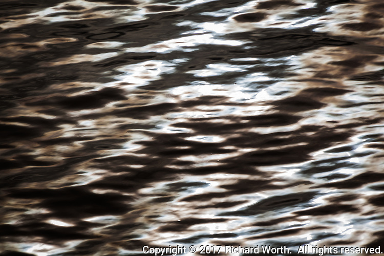 Rippling waters are smoothed by a slow shutter speed and colors are enhanced in software to create an abstract as a standalone piece or background for graphic design.