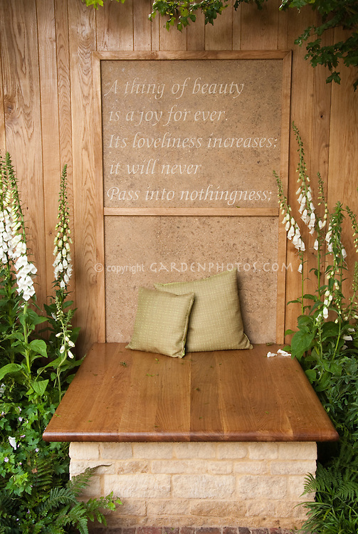John Keats poetry poem quote on garden wall with bench, Digitalis foxglove flowers, pillows, wood and stone, brick patio. A thing of beauty if a joy forever. Its loveliness increases; it will never pass into nothingness. Meditation Zen tranquil garden spot outdoors