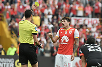 BOGOTÁ - COLOMBIA, 05-11-2017: Wilmar Roldan, árbitro, shows the yellow card to Sebastian Salazar de Santa Fe durante el partido entre Independiente Santa Fe y America de Cali por la fecha 19 de la Liga Aguila II 2017 jugado en el estadio Nemesio Camacho El Campin de la ciudad de Bogota. / Wilmar Roldan, referee, shows the yellow card to Sebastian Salazar of Santa Fe during match between Independiente Santa Fe and America de Cali for the date 19 of the Aguila League II 2017 played at the Nemesio Camacho El Campin Stadium in Bogota city. Photo: VizzorImage/ Gabriel Aponte / Staff