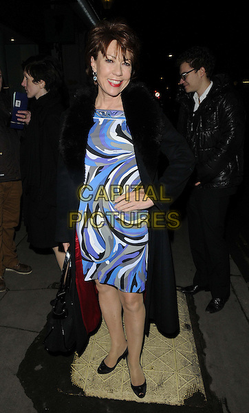 "Kathy Lette.attended the ""Bill Wyman : Reworked"" private view, Rook & Raven, Rathbone Place, London, England..February 26th, 2013.full length black coat blue white dress grey gray pattern print hand on hip fur collar.CAP/CAN.©Can Nguyen/Capital Pictures."