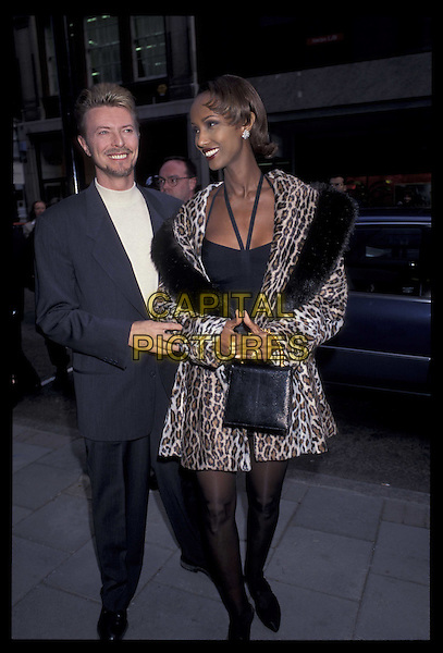 DAVID BOWIE & IMAN.Ref: 1128.full length, full-length, married, celebrity couple.*RAW SCAN- photo will be adjusted for publication*.www.capitalpictures.com.sales@capitalpictures.com.©Capital Pictures