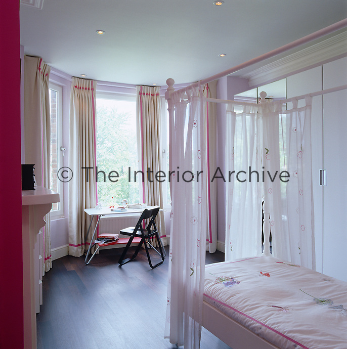 A pale pink four-poster bed is a feature of this light and feminine child's bedroom.