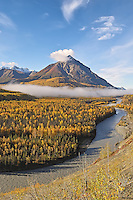The early morning sun burns off a fog bank at the base of King Mountain, along the Matanuska River about 75 miles from Anchorage, Alaska and just downstream from its confluence with the Chickaloon River.
