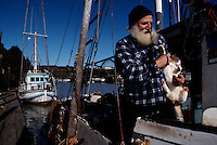 A white bearded fisherman and his cat make their home together on a boat at the Noyo Harbor in Fort Bragg.