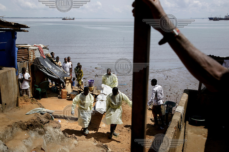 An IFRC Safe and Dignified Burial Team collecting the body of fisherman Mohammed Kamara, 52, from the Ferry Terminal community. According to his family he became seriously ill on 3 November and died 3 days later. Test results later confirmed that he had died from ebola.