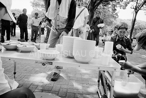 """Nagoya, Japan.June 14, 2009..Rev. Shinji Kinjyo of """"Toukai Chino Hate Senkyou Kyoukai"""" ( End of the Earth Mission Church ) organizes a mass and soup-run for the homeless at Shirakawa Park near Nagoya station. He claims to have been doing a Soup-run for 4 years, twice a week. Recently, he has started to see new people in 20's since the economy had gone bad."""