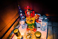 An altar of San Simón (a patron saint of sex workers), surrounded by offerings, is seen placed underneath the bar in a sex club in San Salvador, El Salvador, 9 April 2018. Sex workers' task in the club is to be an entertaining and seductive companion. Performing erotic dance on the pole they make the customers stay as long as possible and buy relatively expensive alcoholic beverages from which they have a certain share. Sex workers are not obliged to have sexual intercourse with the club customers, they decide themselves, usually according to their current economic situation.