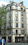 White shuttered windows of apartment block above opticians. Paris France.