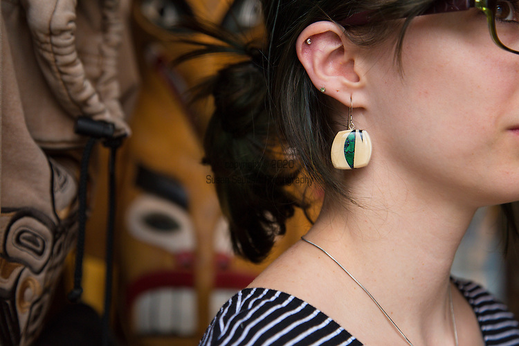 Le Sachem, a store that specializes in Native American Arts located in the Upper Town of Vieux Quebec, Quebec City, Quebec, Canada. A young woman who works at the store models handmade jewelry created from Woolly Mammoth Ivory by Canadian artist Aryn Bowers.  The Ivory is sourced from Siberia and the Klondike mining area of the Yukon Territory.