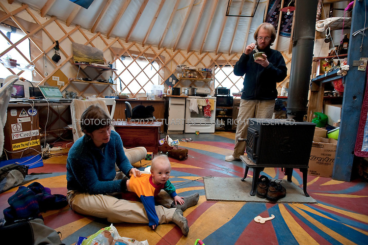 12/11/2009--Seldovia, Alaska, USA..Erin McKittrick changes her son, Katmai's daiper in their yurt in Seldovia, Alaska...The yurt is made by Nomad Shelter in Homer, Alaska, and cost about $14,000.  Bretwood Higman ('Hig'), 33 and Erin McKittrick, 30, built it in November, 2008 on land owned by Hig's mother in Seldovia. The yurt is 24' in diameter, the ceiling is over 12' in the middle, 7' around the edge. It has no running water but does have electricity and internet access...McKittrick grew up in Seattle and met Higman, from Seldovia, at Carleton College in 2001.  In June 2007, the couple left Seattle for the Aleutian Islands, traveling 4000 miles solely by human power through some of the most rugged terrain in the world; their adventure has recently been published in a book written by McKittrick with Hig's photographs titled, 'A Long Trek Home: 4,000 Miles by Boot, Raft, and Ski'...Together, the couple also run a small environmental non-profit, Ground Truth Trekking, which uses trekking to explore the complexities of natural resource issues.  The couple lives with their 10 month old son son, Katmai, in Seldovia, Alaska, a 300 person village just off the end of the road system...©2009 Stuart Isett. All rights reserved.