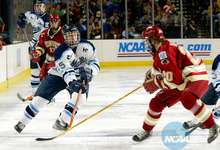 10 APR 2004:  Forward Greg Moore (15) of the University of Maine advances the puck down ice past defender Jussi Halme (20) of Denver University during the Division I Men's Ice Hockey Championship held at the Fleet Center in Boston, MA.  Denver defeated Maine 1-0 for the national title.  Jamie Schwaberow/NCAA Photos