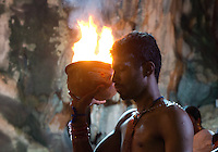 man carrying holy fire in a bowl, walking downstairs into sanctuary of Batu Caves,  Thaipusam ceremonies,   Kuala Lumpur, Malaysia, 2012. Thaipusam ceremonies, celebrated by tamile Hindu community in Malaysia, take place  in Sanctuary of Batu Caves at the border of Kuala Lumpur, each year around end of January or beginning of February, according to Hindu moon calendar. The event is paying hommage to Lord Murugan, a spirit or god created by Shiva to lead the army of gods against the army of evil demons, finally defeating the evil spirits. There are many ways to present offerings or sacrifices for this major religious event. Devotees mortify their bodies by carrying heavy kavaris with spears fixed in their skin or fruits, flowers and little post with holy milk fixed with hooks in their skin, ascending the stairways to the sanctuary in trance, `followed by assistant  taking care and musicians playing loud and fast rhythmic trance music.  Many families shave their head in a ritual before ascending the stairways, as part of rituals to obtain salvation for their ancestors.