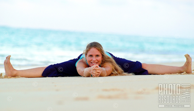 Woman in yoga splits stretch on white sand beach, Hawaii