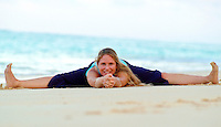 Woman in yoga splits stretch on white sand beach, Hawaii