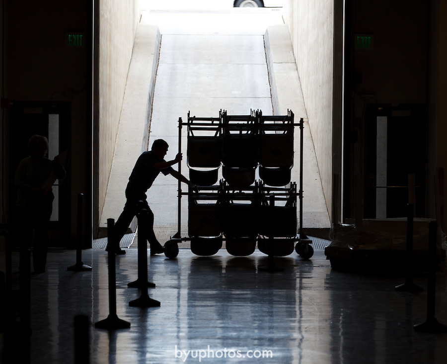 1204-40 2268<br /> <br /> 1204-40 Spring Commencement<br /> <br /> Brigham Young University Graduation<br /> <br /> Student employee pushes cart of chairs past Marriott Center MC entrance, Silhouette.<br /> <br /> February 07, 2009<br /> <br /> Photo by Jaren Wilkey/BYU<br /> <br /> &copy; BYU PHOTO 2012<br /> All Rights Reserved<br /> photo@byu.edu  (801)422-7322