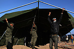 Tunisian soldiers and volunteers erect a tent at a temporary shelter for foreign workers at the Tunisia-Libya border near Ben Guerdane, Tunisia, Friday, Feb. 25, 2011. Thousands crossed the border into Tunisia, fleeing the violence of an uprising in Libya. Opposition forces reportedly have control of much of the country, but Col. Muammar Qaddafi still controls the capital Tripoli.