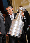 Washington, DC - September 10, 2009 -- United States President Barack Obama carries the Stanley Cup on stage during a ceremony honoring the Pittsburgh Penguins for their 2009 Stanley Cup championship victory,September 10, 2009 in Washington, DC..Credit: Olivier Douliery - Pool via CNP