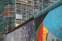 Section of the Berlin Wall including Touch The Wall by Christine Kuhn (left) and Vorsicht by Rodolfo Ricalo (right), part of the East Side Gallery, a 1.3km long section of the Wall on Muhlenstrasse painted in 1990 on its Eastern side by 105 artists from around the world, Berlin, Germany. Many of the artworks are now damaged by graffiti. In the background is a new high-rise building under construction. Picture by Manuel Cohen