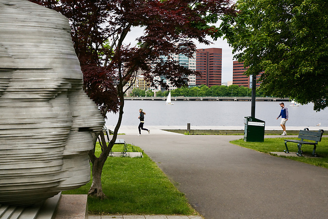 Joggers pass a statue of ARTHUR FIEDLER the conductor of the Boston Pops orchestra in CHARLES RIVER PARK - BOSTON, MASSACHUSETTS