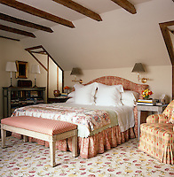 The comfortable guest bedroom has a carpet with a floral motif and an upholstered bench at the foot of the bed