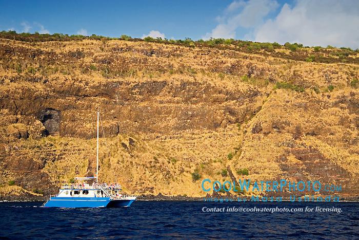 Sheer cliffs of Kealakekua Bay dwarfing 60 foot custom catamaran, Fairwind II, charter boat, Captain Cook, Big Island, Hawaii, Pacific Ocean