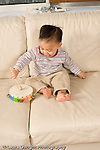 16 month old toddler boy playing musical instrument tambourine hitting it with a drum stick vertical