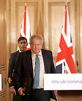 17/03/2020 - Chancellor Rishi Sunak and British Prime Minister Boris Johnson arrive for a press briefing about the ongoing situation with the COVID-19 coronavirus outbreak, inside 10 Downing Street in London. For most people, the new coronavirus causes only mild or moderate symptoms, such as fever and cough. For some, especially older adults and people with existing health problems, it can cause more severe illness, including pneumonia. Photo Credit: ALPR/AdMedia