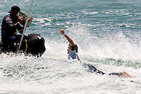 American Brett Simpson with a tow in raises his arm in victory after defeating South African Jordy Smith in the finals during the 2010 US Open of Surfing in Huntington Beach, California on August 8, 2010.