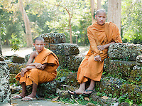 Young Buddhist monks sit on the ruins of a wall at Angkor, Siem Reap, Cambodia