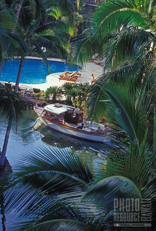 Tourists on shuttle boat in Hilton Waikoloa passing swimming pool, framed by palm trees