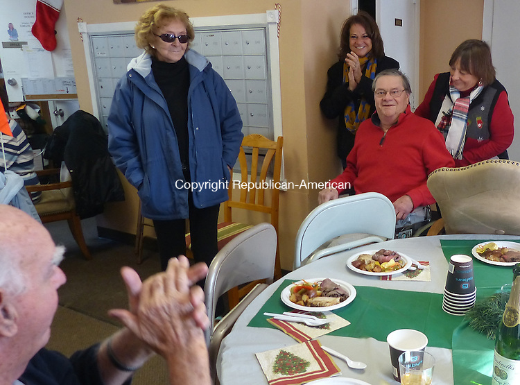 CHESHIRE, CT-19 December 2013-121913BF02- David Giraldi, middle in red, a former resident of the Cheshire Housing Authority's Beachport community, is greeted with applause during his visit Thursday. Giraldi, who lived at the complex for eight years,  returned for the first time since being struck by a pick-up truck while out for a walk on November 3, 2012. David's return to visit old friends was a surprise for residents. With David are from left  Betty Smith, David's sister Lenore Hill from Waterbury, and Janet Norback, right.     Bob Falcetti Republican-American