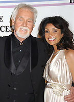 """20 March 2020 - Kenny Rogers, whose legendary music career spanned nearly six decades, has died at the age of 81. Rogers was inducted to the Country Music Hall of Fame in 2013."""" He had 24 No. 1 hits and through his career more than 50 million albums sold in the US alone. He was a six-time Country Music Awards winner and three-time Grammy Award winner. Some of his hits included """"Lady,"""" """"Lucille,"""" """"We've Got Tonight,"""" """"Islands In The Stream,"""" and """"Through the Years."""" His 1978 song """"The Gambler"""" inspired multiple TV movies, with Rogers as the main character. File Photo: 03 December 2006 - Washington, D.C. - Kenny Rogers and wife Wanda. 29th Annual Kennedy Center Honors celebrating Zubin Mehta, Dolly Parton, Andrew Lloyd Webber, Steven Spielberg and William 'Smokey' Robinson held at the John F. Kennedy Center for the Performing Arts. Photo Credit: Laura Farr/AdMedia"""