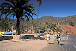 Backpackers returning to Two Harbors, Catalina Island, California Backpackers on sand beach shore returning after camping to Two Harbors, Catalina Island, California