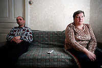 Sasha and Lyuba Boichuk watch a stand-up comedy show during the New Years holiday. Lyuba blames the Chernobyl accident for their son's murder, but Sasha blames himself. At the time of the accident, the Boichuks were just starting to build themselves this house in Sukachi, Ukraine. After some hesitation, they kept building and have lived here ever since. <br /> ------------------- <br /> This photograph is part of Michael Forster Rothbart's After Chernobyl documentary photography project.<br /> &copy; Michael Forster Rothbart 2007-2010.<br /> www.afterchernobyl.com<br /> www.mfrphoto.com <br /> 607-267-4893 o 607-432-5984<br /> 5 Draper St, Oneonta, NY 13820<br /> 86 Three Mile Pond Rd, Vassalboro, ME 04989<br /> info@mfrphoto.com<br /> Photo by: Michael Forster Rothbart<br /> Date:  1/2009    File#:  Canon 5D digital camera frame 6210 <br /> ------------------- <br /> Original caption: .Photo title:.New Year's holiday in Sukachi. ..Short caption: .Lyuba Boichuk blames the Chernobyl accident for their son's murder, but her husband Sasha blames himself...Full caption: .Sasha and Lyuba Boichuk watch a stand-up comedy show on TV during the New Years holiday. At the time of the 1986 accident, Sasha and Lyuba were just starting to build themselves this house in Sukachi. After some hesitation, they decided to continue building and have lived here ever since.  .     Sasha worked as a liquidator in the Chernobyl clean-up efforts. Afterwards, he began to drink heavily, and says he lost a decade of his life to alcohol. He blames himself for the death of his son, who disappeared outside a local bar and is believed to have been murdered during a robbery. .-------------------.