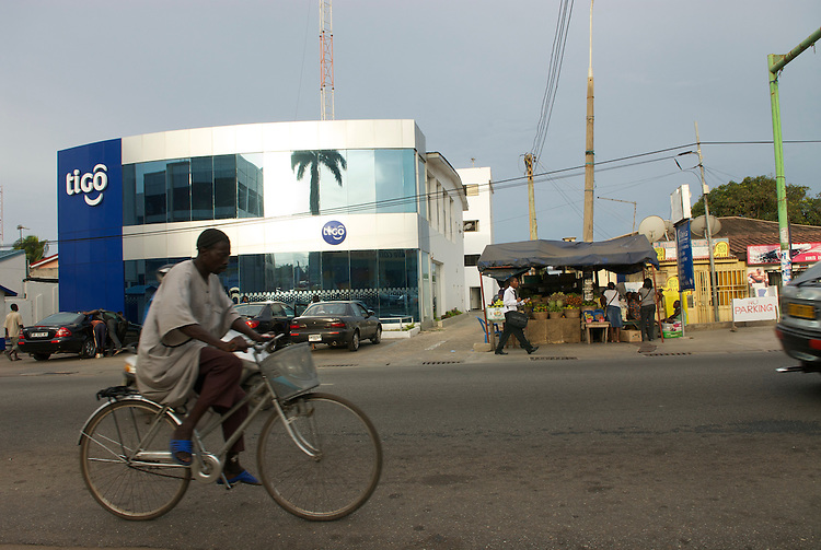 A cyclist and a pedestrian pass the Tigo office  - a Network operator. Street stalls and mirror glass coexist in Osu, central-eastern Accra.