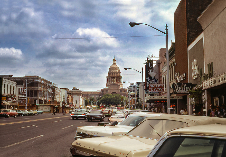 In this retro 1968 photo, antique automobiles of that period parked up and down Congress Avenue leading up to the Texas State Capitol. Retail stores line the streets all the way up to the Texas State Capitol. These stores include Ward's Cut Rate Drugs, Goodfriends, Texas State Optical, J Harris, Lee Optical and the Liberty Cafe.