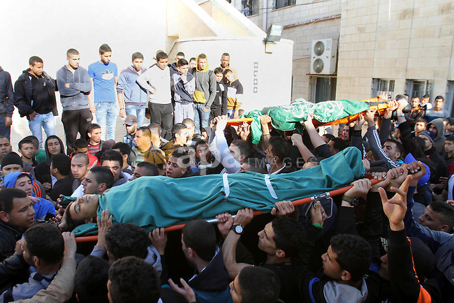 Palestinian look at the bodies of the three Palestinians, including Hamza Abu Al-Heja (R), 20, a member of the Ezzedine al-Qassam Brigades, the military wing of the Palestinian Hamas movement, who were killed during an operation launched by Israeli soldiers in the Jenin refugee camp to arrest al-Heja, during their funeral in the northern West Bank city of Jenin on March 22, 2014. Medical and security sources said that two of those killed were militants and the third was a civilian. Photo by Nedal Eshtayah