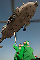 110210-N-7981E-738 ARABIAN SEA (Feb. 10, 2011) Logistics Specialist 2nd Class Omarge McDonald and Logistics Specialist 3rd Class James Kee attach cargo to the underside of an MH-60S Knight Hawk on the flight deck of the Nimitz-class aircraft carrier USS Carl Vinson (CVN 70) during a vertical replenishment-at-sea with the dry cargo/ammunition ship USNS Wally Schirra (T-AKE 8). The Carl Vinson Carrier Strike Group is deployed supporting maritime security operations and theater security cooperation efforts in the U.S. 5th Fleet area of responsibility. (U.S. Navy photo by Mass Communication Specialist 2nd Class James R. Evans / RELEASED)