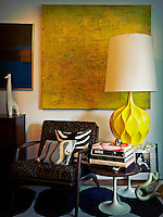 A contemporary yellow artwork hangs on the wall behind a retro style wooden armchair. A large yellow lamp with a white shade is placed on a pedestal side table; books stand on another.