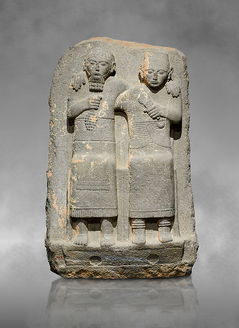 Hittite monumental relief sculpture of of two seated figure, not a typical Hittite style with a lot of other influences. Late Hittite Period - 900-700 BC. Adana Archaeology Museum, Turkey. Against a grey art background